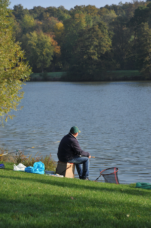 fisherman at the line at the edge of the pond