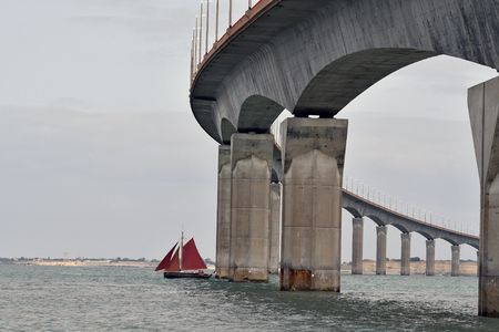 sailboat under the bridge of Re island