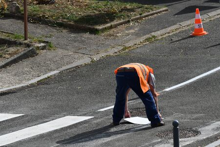 worker drawing a passage for pedestrians