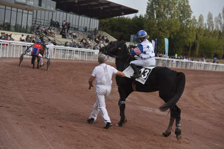 jockey on his racehorse with his trainer