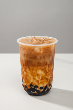 Black tea latte in a transparent glass Stock Photo