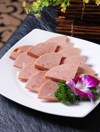 Fresh cut luncheon meat in a white dish