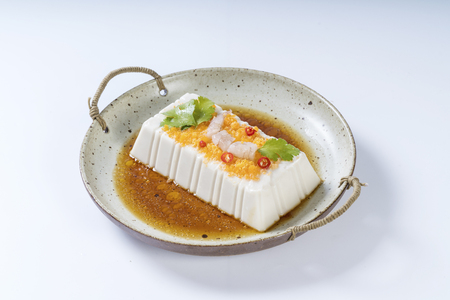 Crab roe tofu with soy sauce in a ceramic dish