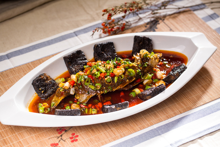 Mandarin fish and stinky tofu in a white ceramic dish