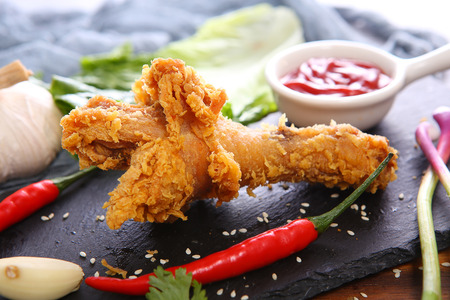 Spicy fried chicken drumstick on a black stone slab Imagens - 121828751
