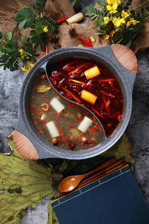 Olio rosso piccante e minestra pulita in una pentola di ceramica