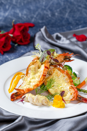 Grilled lobster with cheese in a white ceramic dish
