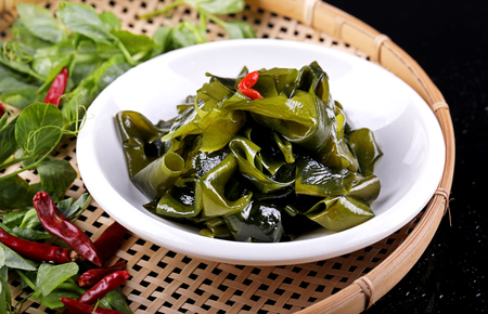 Shredded kelp with soy sauce in a white ceramic dish Фото со стока