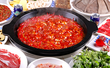 The boiling spicy red oil hotpot soup in a black ceramic pot