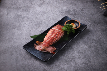 Baked squid served on a black ceramic dish plate