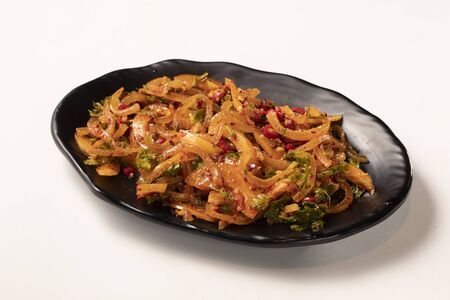 Spicy cold mixed shredded pork meat in a black ceramic dish