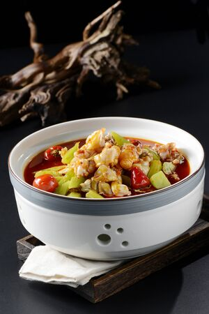 Stewed bullfrog with pickled pepper in a white clay pot