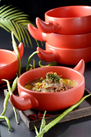 Braised beef tongue with fresh pepper in a red clay pot Archivio Fotografico