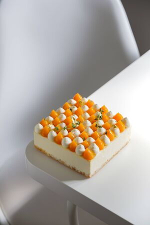 A squarish cream cake with mango and cream