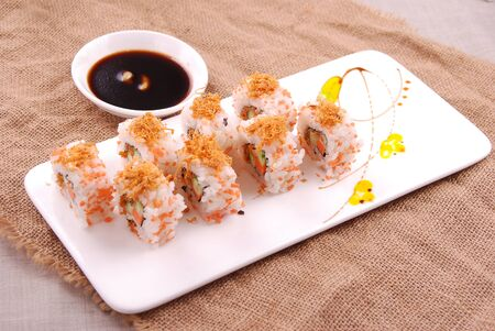 Sushi rolls with sauce in a white ceramic dish