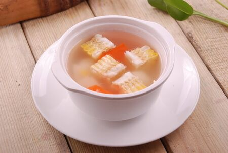 Corn and carrot soup in a white ceramic dish