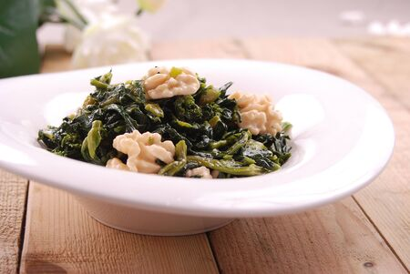 Sauteed fresh ivy in a white ceramic dish Archivio Fotografico