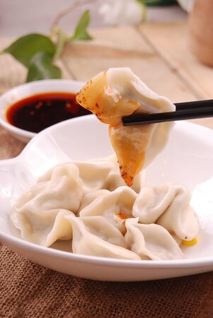 Dip in red oil dumplings in a white ceramic dish Archivio Fotografico - 134834049