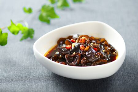 Cold black fungus with vinegar and chili in a white ceramic dish