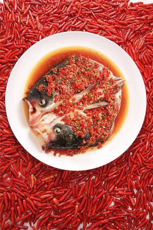 Steamed fish head with chopped chili in a white ceramic dish Archivio Fotografico
