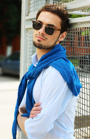 Fashion model macho male front fence outdoor Stock Photo
