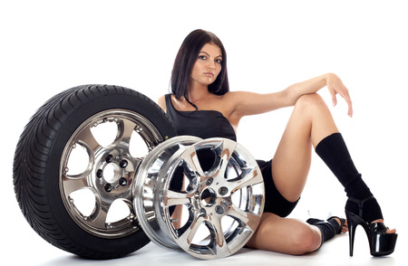 only one girl: Young sexy girl lying near the car wheel and disk, isolated on white