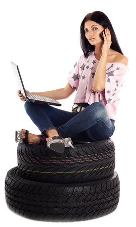 color consultation: Young sexy woman with laptop and mobile sitting on the car wheels, isolated on white.