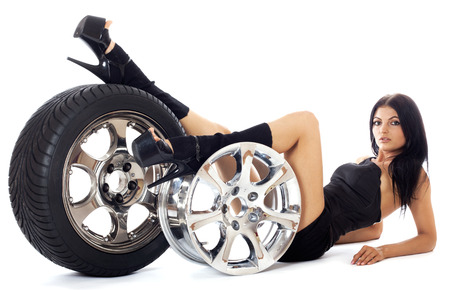 only girls: Young sexy girl lying near the car wheel and disk, isolated on white