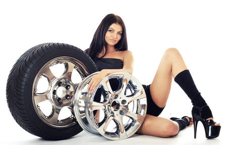 Young sexy girl lying near the car wheel and disk, isolated on white. Stock Photo