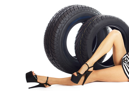 only 1 girl: Young sexy girl lying near the car wheel, isolated on white.