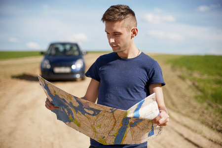Photo of a traveler parked his car by the side of a  road,  lost and reading the map. Focus on the map and male. photo