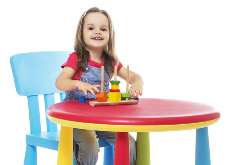 three years old girl sitting at the table and playing, isolated on white