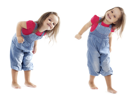 2 persons only: Happy toddler girl wearing jeans jumpsuit is having a great time dancing in the studio. Isolated on white. Stock Photo