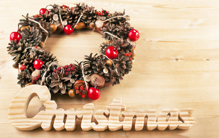 Christmas frame for greeting card with decorative wreath. wooden background photo