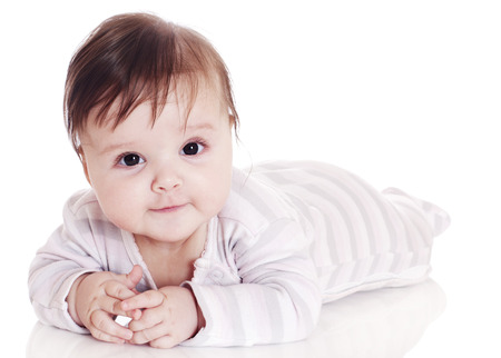 Cute baby lying on stomach on white floor background and smiling big. photo
