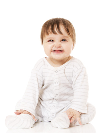 coif: Cute baby sitting on the white floor background, wearing a sliders and smiling big. Isolated. Stock Photo