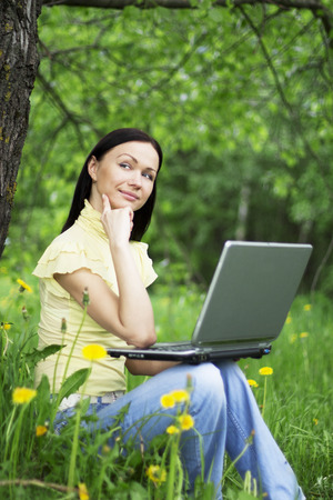 Young woman sitting on the grass with laptop on her knees and thinking about the future or past. photo