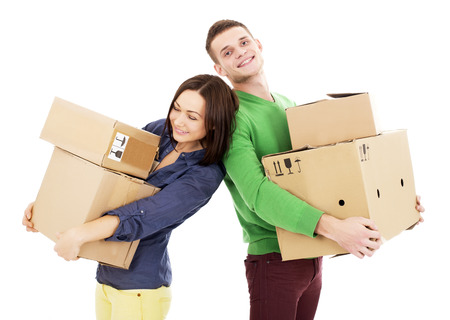 2 persons only: Young couple smile while holding large cardboard boxes. Vertical shot. Isolated on white. Stock Photo