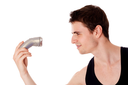 Young man shaving his beard off with an electric razor, isolated on white. photo