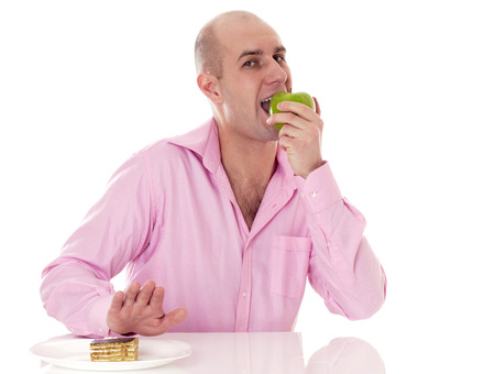 Caucasian man eating apple instead of cake, isolated on white background. Stock Photo