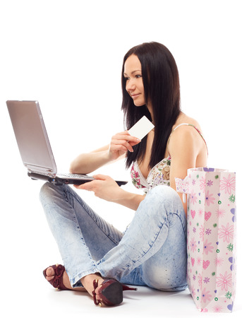 contemplates: Beautiful woman contemplates her online purchase. Isolated on white.