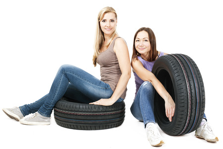 two persons only: Two young girls sitting on the car wheels, isolated on white.