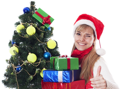 Beautiful young woman with gifts next to christmas tree showing OK sign and winking, isolated on white background. photo