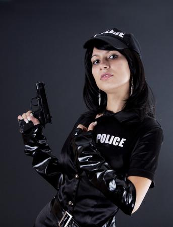 gorra policía: hermosa mujer policía con esposas en un uniforme negro que apunta un arma. Aislado en negro. Foto de archivo