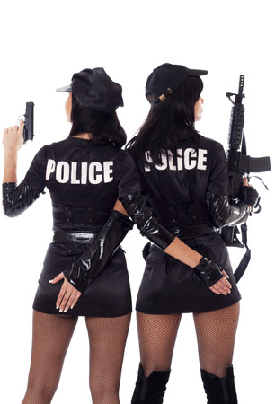 policewomen: two beautiful policewomen with handcuffs in a black uniform that aiming a submachine gun. Isolated on white. Stock Photo