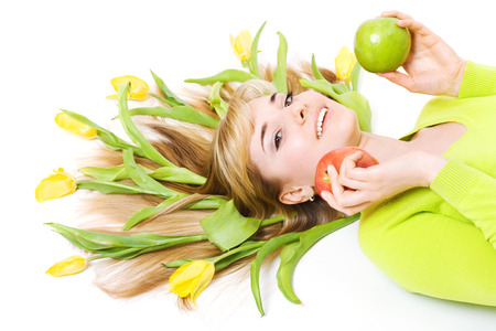 Smiling woman with apple and bouquet of tulips in her hair, isolated on white photo
