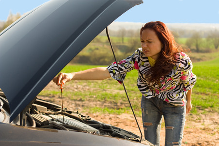 bent over: young woman with oil probe bent over car engine