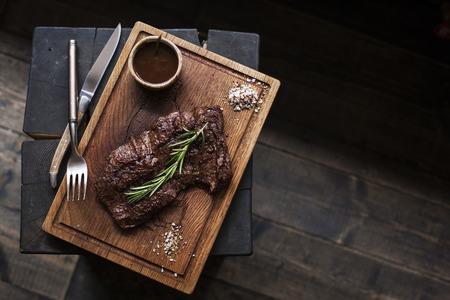 Biefstuk. Stuk van Gegrilde BBQ rundvlees gemarineerd in specerijen en kruiden op een rustieke houten bord op een ruwe houten bureau met een kopie ruimte. Bovenaanzicht