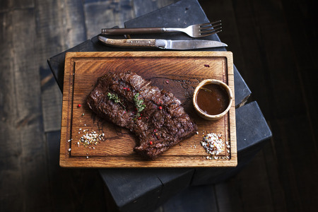 dark meat: Beef steak. Piece of  Grilled BBQ beef marinated in spices and herbs on a rustic wooden board over rough wooden desk with a copy space. Top view Stock Photo