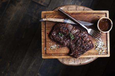 牛肉のステーキ。コピー スペースで大まかな木製机の上スパイスと素朴な木の板にハーブでマリネしたグリル バーベキュー牛肉の部分。トップ ビ 写真素材